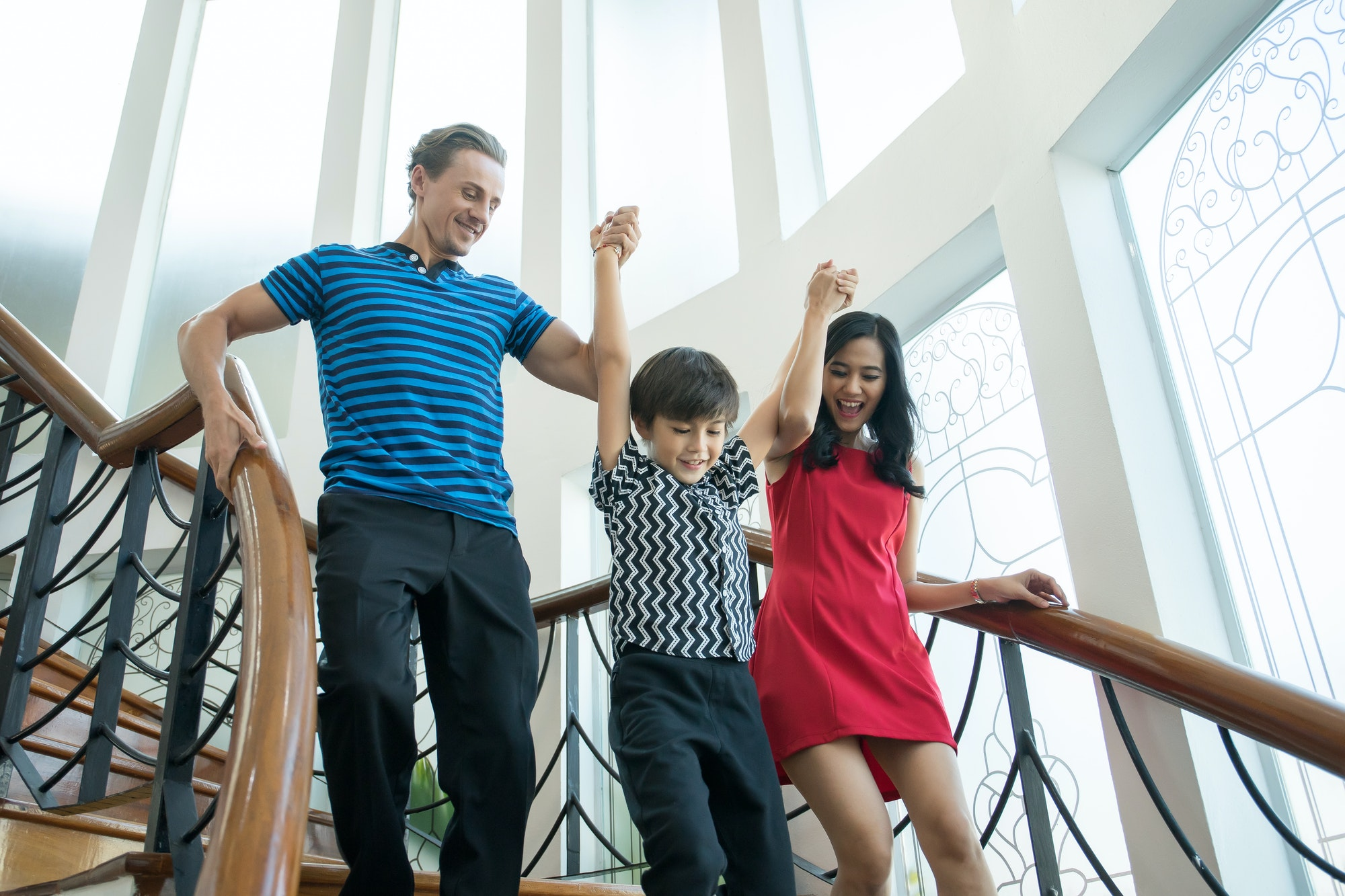 Family walk down the stairs in the house.